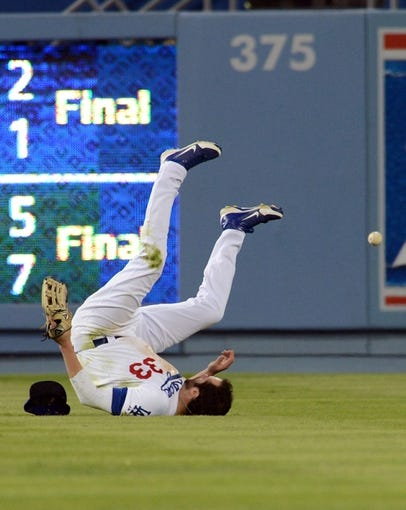 Sep 28, 2013; Los Angeles, CA, USA;   Los Angeles Dodgers left fielder Scott Van Slyke (33) rolls after missing a ball in the outfield in the fourth inning of the game against the Colorado Rockies at Dodger Stadium. Mandatory Credit: Jayne Kamin-Oncea-USA TODAY Sports