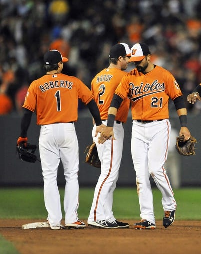 Sep 28, 2013; Baltimore, MD, USA; Baltimore Orioles teammates Brian Roberts (1) and Nick Markais (21) celebrate after a game against the Boston Red Sox at Oriole Park at Camden Yards. The Orioles defeated the Red Sox 6-5. Mandatory Credit: Joy R. Absalon-USA TODAY Sports