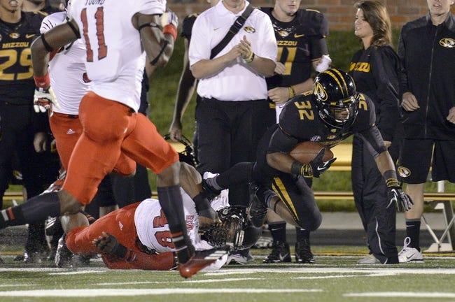Sep 28, 2013; Columbia, MO, USA; Missouri Tigers running back Russell Hansbrough (32) is tackled by Arkansas State Red Wolves linebacker Qushaun Lee (48) during the second half at Faurot Field. Mandatory Credit: Jasen Vinlove-USA TODAY Sports