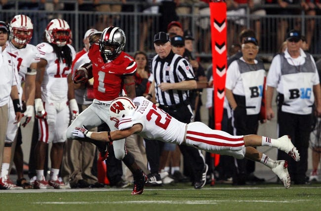 Sep 28, 2013; Columbus, OH, USA; Ohio State Buckeyes running back Dontre Wilson (1) gets pushed out of bounds by Wisconsin Badgers safety Kyle Zuleger (27) during the fourth quarter at Ohio Stadium. Buckeyes beat the Badgers 31-24. Mandatory Credit: Raj Mehta-USA TODAY Sports