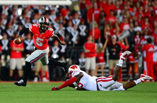 Sep 28, 2013; Columbus, OH, USA; Ohio State Buckeyes quarterback Braxton Miller (5) escapes a Wisconsin Badgers defender during the first quarter at Ohio Stadium. Mandatory Credit: Andrew Weber-USA TODAY Sports