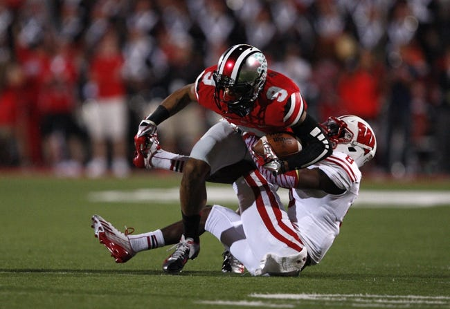 Sep 28, 2013; Columbus, OH, USA; Ohio State Buckeyes wide receiver Devin Smith (9) gets tackled by Wisconsin Badgers cornerback Sojourn Shelton (8) during the fourth quarter at Ohio Stadium. Buckeyes beat the Badgers 31-24. Mandatory Credit: Raj Mehta-USA TODAY Sports