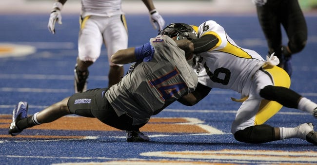 Sep 28, 2013; Boise, ID, USA; Boise State Broncos wide receiver Troy Ware (14) has his helmet taken off during the tackle by Southern Miss Golden Eagles defensive back Kelsey Douglas (6) during the second half against the Southern Miss Golden Eagles at Bronco Stadium. Boise State defeated Southern Miss 60-7. Mandatory Credit: Brian Losness-USA TODAY Sports