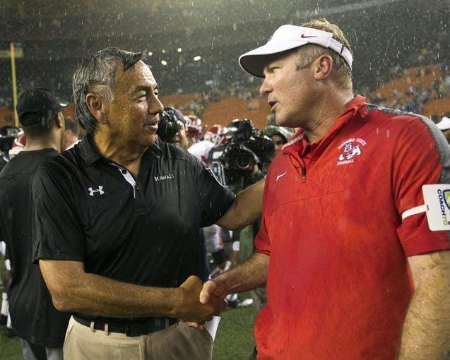 Sep 28, 2013; Honolulu, HI, USA; Hawaii head coach Norm Chow congratulates Fresno State head coach Tim DeRuyter after Fresno State defeated Hawaii 43-37 in the NCAA college football game at Aloha Stadium. Mandatory Credit: Marco Garcia-USA TODAY Sports