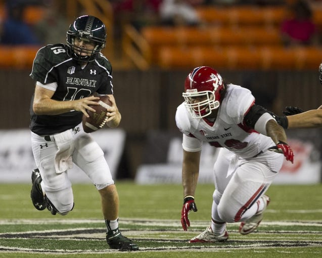 Sep 28, 2013; Honolulu, HI, USA;  Hawaii quarterback Sean Schroeder (19) scrambles away from Fresno State defensive back Sean Alston (18) during the fourth quarter of the NCAA college football game at Aloha Stadium. Mandatory Credit: Marco Garcia-USA TODAY Sports