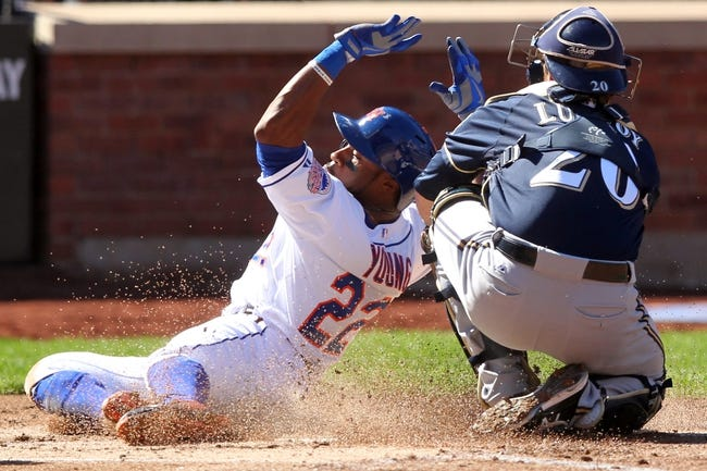 Sep 29, 2013; New York, NY, USA; New York Mets left fielder Eric Young Jr. (22) scores a run ahead of a tag by Milwaukee Brewers catcher Jonathan Lucroy (20) during the first inning of a game at Citi Field. Mandatory Credit: Brad Penner-USA TODAY Sports