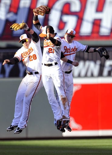 Sep 29, 2013; Baltimore, MD, USA; Baltimore Orioles outfielders Steve Pearce (left), Nick Markakis (center), and Nate McLouth (right) celebrate after the game against the Boston Red Sox at Oriole Park at Camden Yards. The Orioles won 7-6. Mandatory Credit: Joy R. Absalon-USA TODAY Sports