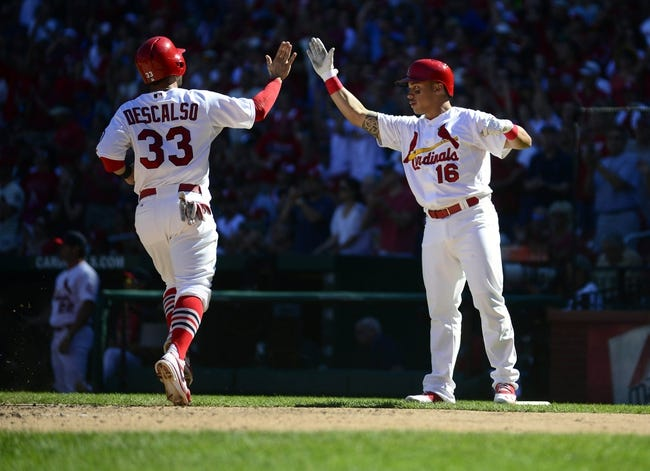 Sep 29, 2013; St. Louis, MO, USA; St. Louis Cardinals second baseman Kolten Wong (16) high fives shortstop Daniel Descalso (33) after he scored on a single by right fielder Shane Robinson (not pictured) during the fourth inning against the Chicago Cubs at Busch Stadium. St. Louis defeated Chicago 4-0 and clinched the best record in the National League. Mandatory Credit: Jeff Curry-USA TODAY Sports