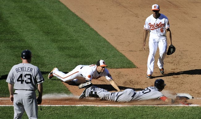 Sep 29, 2013; Baltimore, MD, USA; Boston Red Sox right fielder Quintin Berry (50) is safe at first after laying down a bunt as Baltimore Orioles first  baseman Ryan Flaherty (3) cannot make the tag in the sixth inning at Oriole Park at Camden Yards. The Orioles won 7-6. Mandatory Credit: Joy R. Absalon-USA TODAY Sports