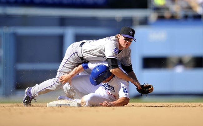 September 29, 2013; Los Angeles, CA, USA; Los Angeles Dodgers second baseman Skip Schumaker (55) is out at second after Colorado Rockies second baseman Josh Rutledge (14) throws to first to complete a double play in the fifth inning at Dodger Stadium. Mandatory Credit: Gary A. Vasquez-USA TODAY Sports
