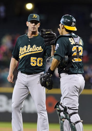 Sep 29, 2013; Seattle, WA, USA; Oakland Athletics relief pitcher Grant Balfour (50) and Oakland Athletics catcher Kurt Suzuki (22) celebrate after defeating the Seattle Mariners at Safeco Field. Oakland defeated Seattle 9-0. Mandatory Credit: Steven Bisig-USA TODAY Sports