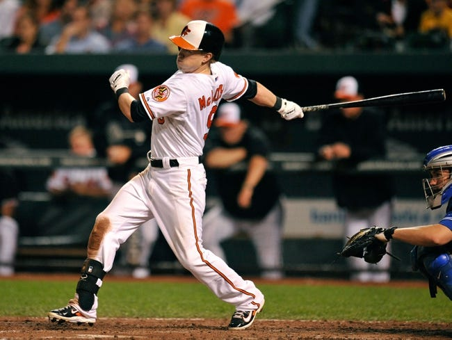 Sep 25, 2013; Baltimore, MD, USA; Baltimore Orioles left fielder Nate McLouth (9) bats in the sixth inning against the Toronto Blue Jays at Oriole Park at Camden Yards. The Orioles defeated the Blue Jays 9-5. Mandatory Credit: Joy R. Absalon-USA TODAY Sports
