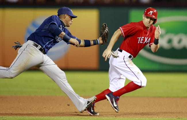 Sep 30, 2013; Arlington, TX, USA; Texas Rangers second baseman Ian Kinsler (right) is tagged out in a run down by Tampa Bay Rays shortstop Yunel Escobar (left) during the third inning at Rangers Ballpark at Arlington. Mandatory Credit: Tim Heitman-USA TODAY Sports