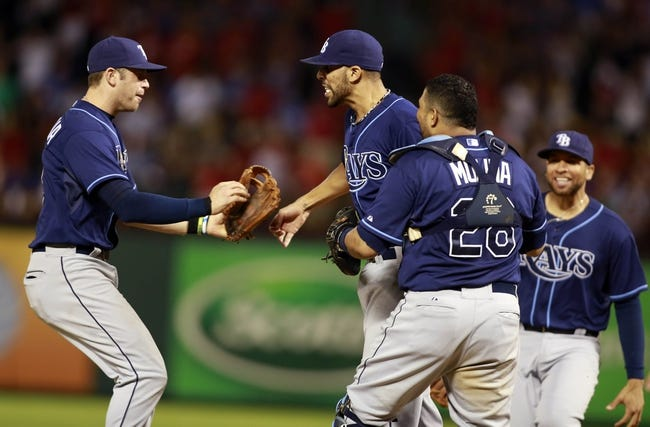Sep 30, 2013; Arlington, TX, USA; Tampa Bay Rays starting pitcher David Price (middle) celebrates with teammates Evan Longoria (left) , Jose Molina (28) and James Loney (right) after defeating the Texas Rangers 5-2 at Rangers Ballpark at Arlington. Mandatory Credit: Tim Heitman-USA TODAY Sports