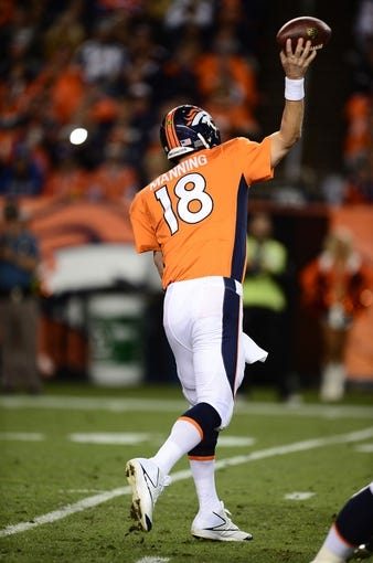 Sep 23, 2013; Denver, CO, USA; Denver Broncos quarterback Peyton Manning (18) passes against the Oakland Raiders in the second quarter at Sports Authority Field at Mile High. Mandatory Credit: Ron Chenoy-USA TODAY Sports