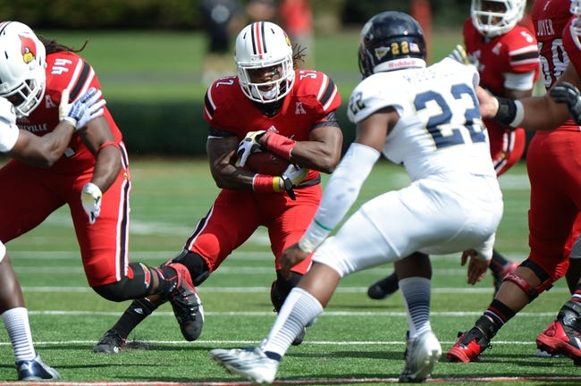 Sep 21, 2013; Louisville, KY, USA; Louisville Cardinals running back Senorise Perry (32) runs the ball against the FIU Golden Panthers during the first quarter of play at Papa John's Cardinal Stadium. Louisville defeated FIU 72-0.  Mandatory Credit: Jamie Rhodes-USA TODAY Sports