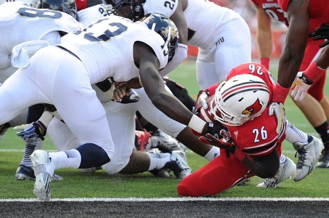 Sep 21, 2013; Louisville, KY, USA; Louisville Cardinals running back Michael Dyer (26) dives past FIU Golden Panthers linebacker Patrick Jean (13) into the end zone to score a touchdown during the second half of play at Papa John's Cardinal Stadium. Louisville defeated FIU 72-0.  Mandatory Credit: Jamie Rhodes-USA TODAY Sports