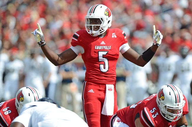 Sep 21, 2013; Louisville, KY, USA; Louisville Cardinals quarterback Teddy Bridgewater (5) makes a call at the line of scrimmage during the first quarter of play against the FIU Golden Panthers  at Papa John's Cardinal Stadium. Louisville defeated FIU 72-0.  Mandatory Credit: Jamie Rhodes-USA TODAY Sports