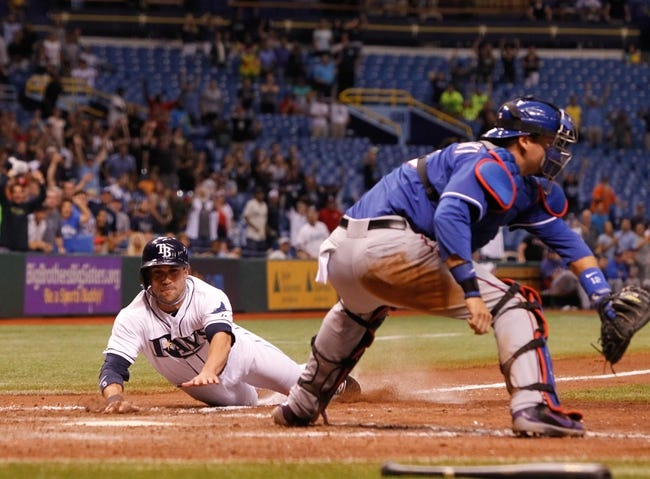 Sep 18, 2013; St. Petersburg, FL, USA; Tampa Bay Rays left fielder Sam Fuld (5) slides safely into home plate to score the winning run as Texas Rangers catcher A.J. Pierzynski (12) attempted to tag him out during the twelfth inning at Tropicana Field. Tampa Bay Rays defeated the Texas Rangers 4-3 in twelve inning. Mandatory Credit: Kim Klement-USA TODAY Sports