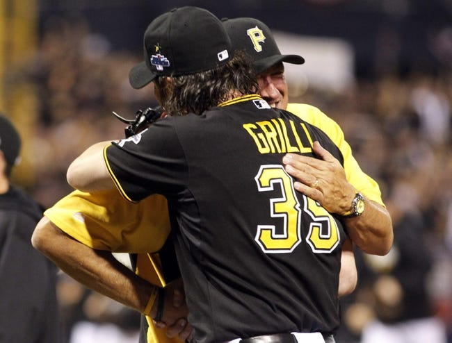 Oct 1, 2013; Pittsburgh, PA, USA; Pittsburgh Pirates relief pitcher Jason Grilli (39) gets a hug from manager Clint Hurdle after defeating the Cincinnati Reds in the National League wild card playoff baseball game at PNC Park. The Pirates won 6-2. Mandatory Credit: Charles LeClaire-USA TODAY Sports