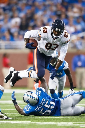 Sep 29, 2013; Detroit, MI, USA; Chicago Bears tight end Martellus Bennett (83) runs the ball trying to avoid a tackle by Detroit Lions middle linebacker Stephen Tulloch (55) in the fourth quarter at Ford Field. Detroit won 40-32. Mandatory Credit: Rick Osentoski-USA TODAY Sports