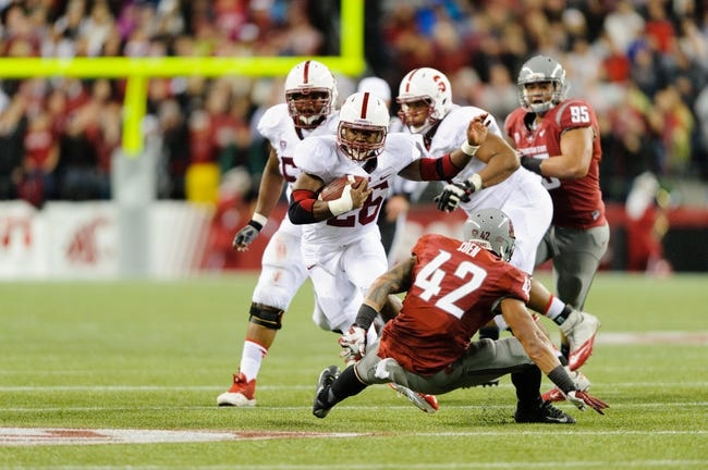 Sep 28, 2013; Seattle, WA, USA; Stanford Cardinal running back Barry Sanders (26) carries the ball past Washington State Cougars linebacker Cyrus Coen (42) during the game at CenturyLink Field. Stanford defeated Washington State 55-17. Mandatory Credit: Steven Bisig-USA TODAY Sports