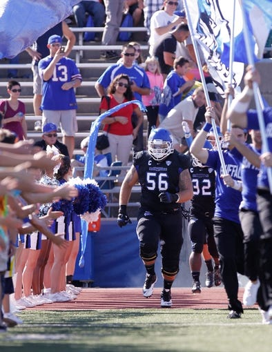 Sep 28, 2013; Buffalo, NY, USA; Buffalo Bulls offensive linesman Jasen Carlson (56) runs out to begin the game between the Buffalo Bulls and the Connecticut Huskies at University of Buffalo Stadium. Buffalo beat Connecticut 41-12. Mandatory Credit: Kevin Hoffman-USA TODAY Sports