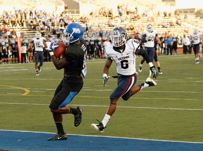 Sep 28, 2013; Buffalo, NY, USA; Buffalo Bulls wide receiver Fred Lee (18) scores a touchdown as Connecticut Huskies cornerback Jhavon Williams (6) pursues at University of Buffalo Stadium. Buffalo beat Connecticut 41-12. Mandatory Credit: Kevin Hoffman-USA TODAY Sports