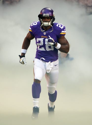Sep 29, 2013; London, UNITED KINGDOM; Minnesota Vikings running back Adrian Peterson (28) runs onto the field through a cloud of smoke before the game against the Pittsburgh Steelers in the NFL International Series game at Wembley Stadium. Mandatory Credit: Kirby Lee-USA TODAY Sports