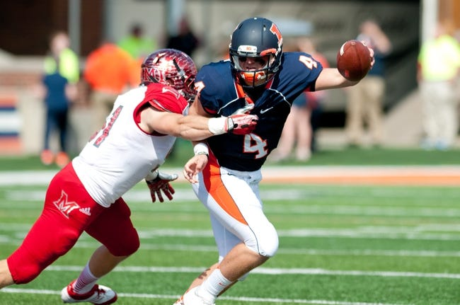 Sep 28, 2013; Champaign, IL, USA; Illinois Fighting Illini quarterback Reilly O'Toole (4) tries to avoid a tackle by Miami (Oh) Redhawks linebacker Josh Dooley (51) at Memorial Stadium. Mandatory Credit: Bradley Leeb-USA TODAY Sports