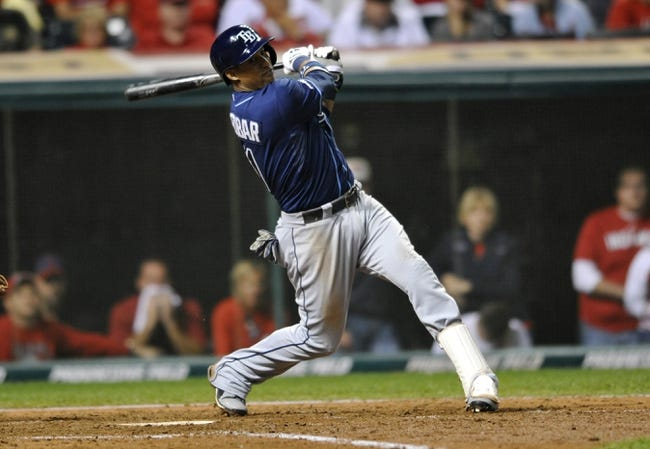Oct 2, 2013; Cleveland, OH, USA; Tampa Bay Rays shortstop Yunel Escobar (11) hits an RBI single against the Cleveland Indians during the 9th inning in the American League wild card playoff game at Progressive Field. Mandatory Credit: David Richard-USA TODAY Sports