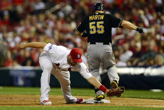Oct 3, 2013; St. Louis, MO, USA; St. Louis Cardinals first baseman Matt Adams (53) forces out Pittsburgh Pirates catcher Russell Martin (55) during the eighth inning in game one of the National League divisional series playoff baseball game at Busch Stadium. St. Louis defeated Pittsburgh 9-1. Mandatory Credit: Jeff Curry-USA TODAY Sports