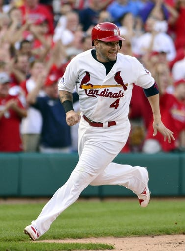 Oct 3, 2013; St. Louis, MO, USA; St. Louis Cardinals catcher Yadier Molina (4) reacts as he scores a run against the Pittsburgh Pirates in game one of the National League divisional series playoff baseball game at Busch Stadium. The Cardinals defeated the Pirates 9-1. Mandatory Credit: Scott Rovak-USA TODAY Sports