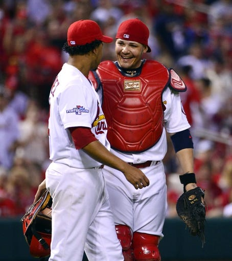 Oct 3, 2013; St. Louis, MO, USA; St. Louis Cardinals relief pitcher Carlos Martinez (left) is congratulated by Cardinals catcher Yadier Molina (right) after throwing out Pittsburgh Pirates catcher Russell Martin (not pictured) in the eighth inning in game one of the National League divisional series playoff baseball game at Busch Stadium. The Cardinals defeated the Pirates 9-1. Mandatory Credit: Scott Rovak-USA TODAY Sports