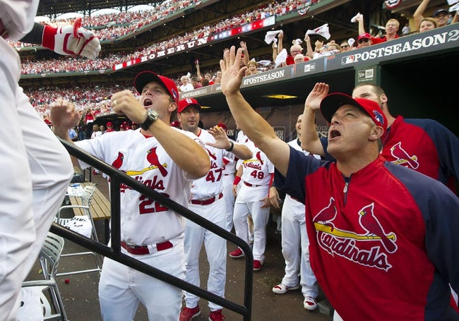 Oct 3, 2013; St. Louis, MO, USA; St. Louis Cardinals manager Mike Matheny (22) and other coaches celebrate a run against the Pittsburgh Pirates in game one of the National League divisional series playoff baseball game at Busch Stadium. The Cardinals defeated the Pirates 9-1. Mandatory Credit: Scott Rovak-USA TODAY Sports