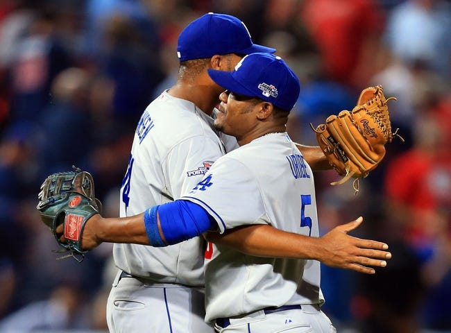 Oct 3, 2013; Atlanta, GA, USA; Los Angeles Dodgers third baseman Juan Uribe (5) hugs relief pitcher Kenley Jansen (74) after defeating the Atlanta Braves in game one of the National League divisional series playoff baseball game at Turner Field. The Dodgers won 6-1. Mandatory Credit: Daniel Shirey-USA TODAY Sports
