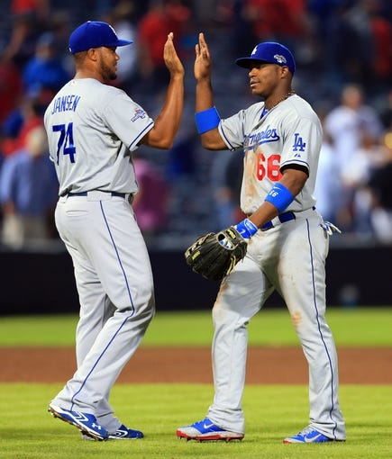 Oct 3, 2013; Atlanta, GA, USA; Los Angeles Dodgers relief pitcher Kenley Jansen (74) high fives right fielder Yasiel Puig (66) after defeating the Atlanta Braves in game one of the National League divisional series playoff baseball game at Turner Field. The Dodgers won 6-1. Mandatory Credit: Daniel Shirey-USA TODAY Sports