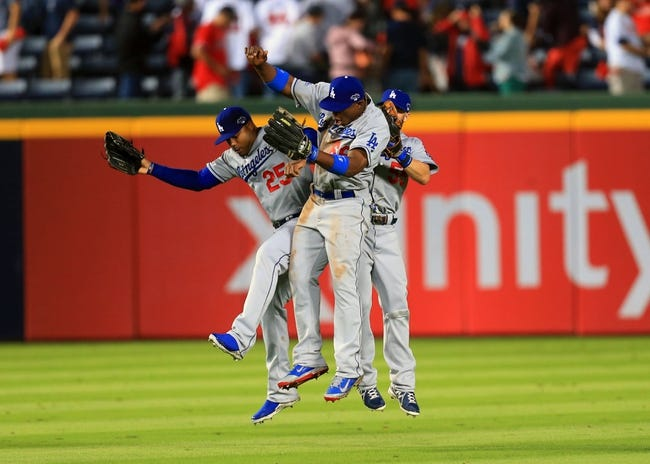 Oct 3, 2013; Atlanta, GA, USA; Los Angeles Dodgers left fielder Carl Crawford (25), right fielder Yasiel Puig (66), and center fielder Skip Schumaker (55) celebrate after defeating the Atlanta Braves in game one of the National League divisional series playoff baseball game at Turner Field. The Dodgers won 6-1. Mandatory Credit: Daniel Shirey-USA TODAY Sports
