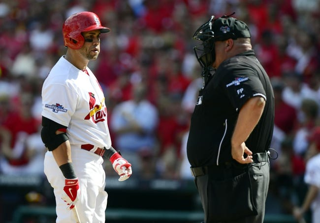 Oct 4, 2013; St. Louis, MO, USA; St. Louis Cardinals right fielder Carlos Beltran (left) argues with home plate umpire Wally Bell (right) after striking out looking in the sixth inning in game two of the National League divisional series playoff baseball game against the Pittsburgh Pirates at Busch Stadium. Mandatory Credit: Jeff Curry-USA TODAY Sports