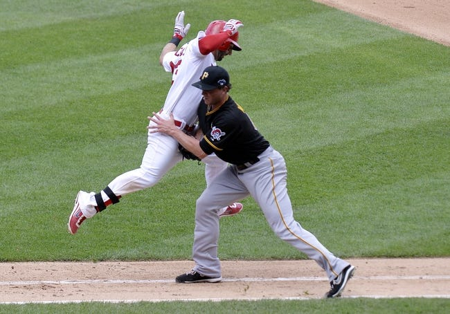 Oct 4, 2013; St. Louis, MO, USA; St. Louis Cardinals shortstop Daniel Descalso (in white) is tagged out by Pittsburgh Pirates relief pitcher Tony Watson in the seventh inning in game two of the National League divisional series playoff baseball game at Busch Stadium. Mandatory Credit: Jasen Vinlove-USA TODAY Sports