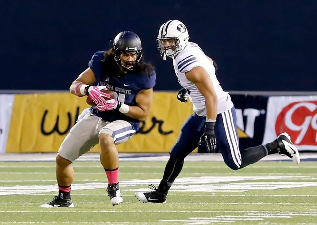Oct 4, 2013; Logan, UT, USA; Utah State Aggies tight end D.J. Tialavea (91) catches the ball and tries to turn as Brigham Young Cougars linebacker Kyle Van Noy (3) looks to tackle Tialavea during the second quarter at Romney Stadium. Mandatory Credit: Chris Nicoll-USA TODAY Sports