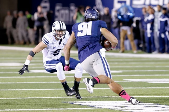 Oct 4, 2013; Logan, UT, USA; Utah State Aggies tight end D.J. Tialavea (91) runs the ball up the field while Brigham Young Cougars defensive back Daniel Sorensen (9) closes in during the second half at Romney Stadium. BYU won 31-14. Mandatory Credit: Chris Nicoll-USA TODAY Sports