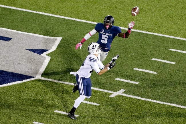 Oct 4, 2013; Logan, UT, USA; Brigham Young Cougars wide receiver Kurt Henderson (13) looks to catch the ball while Utah State Aggies safety Maurice Alexander (5) tries to defend during the fourth quarter at Romney Stadium. BYU won 31-14. Mandatory Credit: Chris Nicoll-USA TODAY Sports