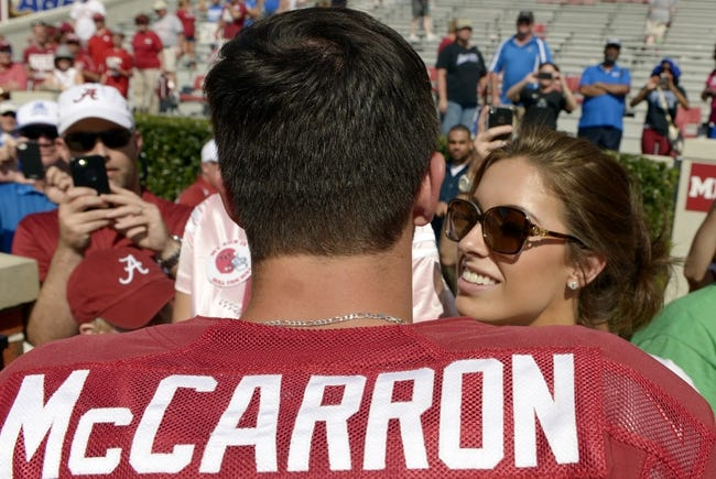 Oct 5, 2013; Tuscaloosa, AL, USA; Katherine Webb kisses Alabama Crimson Tide quarterback A.J. McCarron (10) alongside the fence after the Tides 45-3 victory over the Georgia State Panthers at Bryant-Denny Stadium. Mandatory Credit: John David Mercer-USA TODAY Sports
