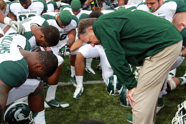 Oct 5, 2013; Iowa City, IA, USA;  Michigan State Spartans coach Mark Dantonio huddles with his team after their game against the Iowa Hawkeyes at Kinnick Stadium. Michigan State beat Iowa 26-14.  Mandatory Credit: Reese Strickland-USA TODAY Sports
