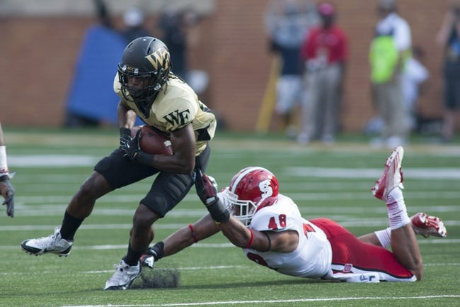 Oct 5, 2013; Winston-Salem, NC, USA; Wake Forest Demon Deacons wide receiver Sherman Ragland III (26) runs after making a catch while being pursued by North Carolina State Wolfpack linebacker Bryan Smith (48) during the first quarter at BB&T Field. Mandatory Credit: Jeremy Brevard-USA TODAY Sports