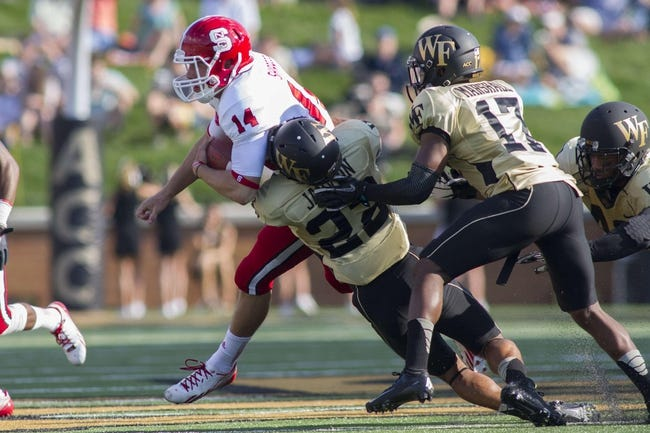 Oct 5, 2013; Winston-Salem, NC, USA; North Carolina State Wolfpack quarterback Bryant Shirreffs (14) gets brought down by Wake Forest Demon Deacons safety Ryan Janvion (22) during the second quarter at BB&T Field. Mandatory Credit: Jeremy Brevard-USA TODAY Sports