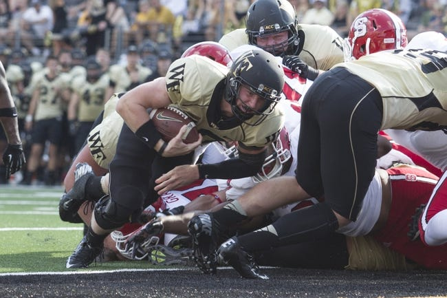 Oct 5, 2013; Winston-Salem, NC, USA; Wake Forest Demon Deacons quarterback Tanner Price (10) dives in for the touchdown during the second quarter against the North Carolina State Wolfpack at BB&T Field. Mandatory Credit: Jeremy Brevard-USA TODAY Sports