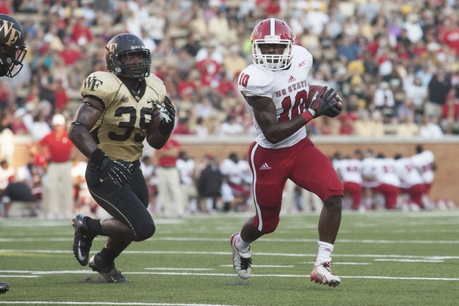 Oct 5, 2013; Winston-Salem, NC, USA; North Carolina State Wolfpack running back Shadrach Thornton (10) runs the ball while being pursued by Wake Forest Demon Deacons linebacker Justin Jackson (39) during the third quarter at BB&T Field. Wake defeated North Carolina State 28-13. Mandatory Credit: Jeremy Brevard-USA TODAY Sports