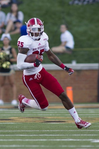 Oct 5, 2013; Winston-Salem, NC, USA;North Carolina State Wolfpack cornerback Dontae Johnson (25) returns an interception during the third quarter against the Wake Forest Demon Deacons at BB&T Field. Wake defeated North Carolina State 28-13. Mandatory Credit: Jeremy Brevard-USA TODAY Sports